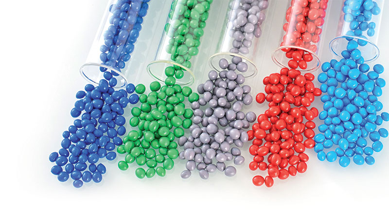 Blue, green, gray, red, and blue TPE pellets/granules for production of menstrual cups coming out of transparent tubes