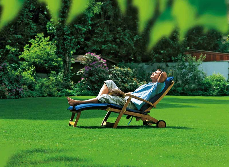 Man resting in chair on a perfect lawn